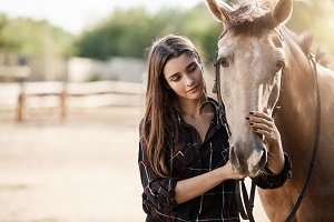 Young female assistant farm manager caring about a horse.