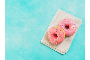 pink donuts on blue background , copy space, top view
