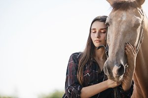 Portrait of a young girl interacting with a horse with closed eyes trying to calm the animal.