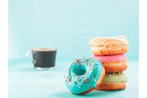 donuts and coffee on blue background , copy space