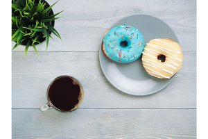 donuts and coffee on gray wooden background, copy space, top view