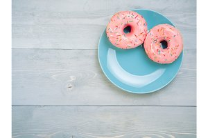 pink donuts on gray wooden background, copy space, top view