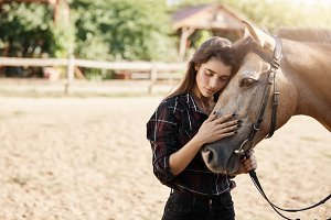 Young cowgirl taking care and calming down a stallion