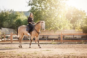 Young female farm manager riding a horse on a ranch on a sunny summer day.