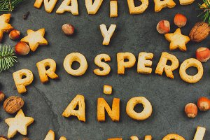 FELIZ NAVIDAD COOKIES. Words text Merry Christmas and Happy New Year en Spanish with baked cookies, Christmas decoration and nuts on black slate background. Christmas card for hispanic countries top view