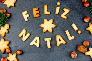 FELIZ NATAL COOKIES. Words Merry Christmas en portuguese with baked cookies, Christmas decoration and nuts on black slate background. Christmas card for portuguese speaking countries top view.