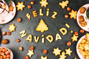 FELIZ NAVIDAD COOKIES. Words Merry Christmas en Spanish with baked cookies, Christmas decoration and nuts on black slate background. Christmas card for hispanic countries top view