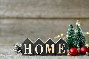Christmas composition with Shining lights. Red balls, Pine cones, toy houses text Home on Wooden Table