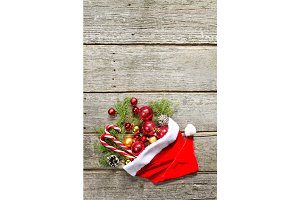 Red santa claus hat with christmas composition balls, toys, candy, fir branches on vintage wooden background