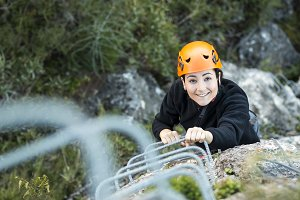 Woman climbing up a via ferrata