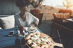 Beautiful girl eating pizza outdoors