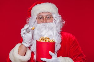 Traditional Santa Claus watching TV, eating popcorn. Christmas. Red background. emotions fear surprise