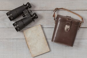 Antique binoculars and notebook on w