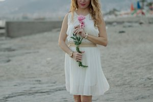 Beautiful woman in ivory dress holding pink eustoma