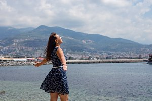 Woman enjoying the view of Mediterranean town with hands spread