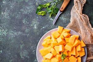 Raw chopped pumpkin on concrete background