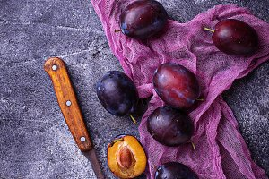 Fresh sweet plums on concrete background