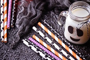 Colorful festive striped paper straws and Halloween decor