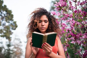 afro woman reading a book outdoors