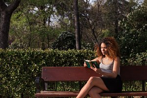 afro woman reading a book on a bench