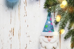Christmas tree branch with blue toys on white wooden background
