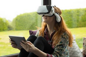 Young woman using vr glasses while sitting on alcove window seat