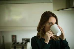 Woman looking away while having coffee at home