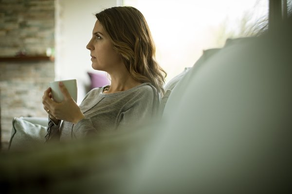 Thoughtful woman having coffee at h…