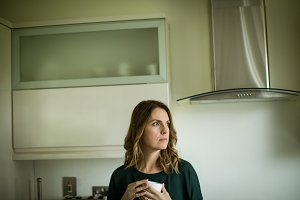 Thoughtful woman holding coffee cup while looking away