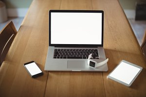 Laptop and electronic devices on wooden table
