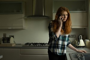 Woman looking away while talking on smartphone