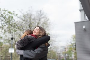 Smiling female friends embracing