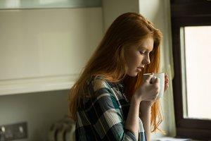 Side view of woman having coffee
