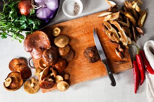 ingredients for cooking mushrooms on cutting board on grey stone
