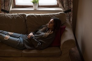 High angle view of woman relaxing on sofa