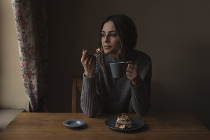 Thoughtful woman having breakfast