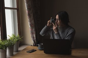 Woman photographing while sitting by window