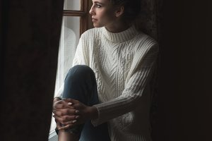Full length of thoughtful young woman sitting on window sill