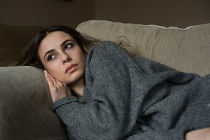 Thoughtful woman looking away while lying on sofa