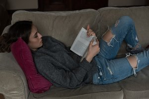 Side view of woman reading book while reclining on sofa