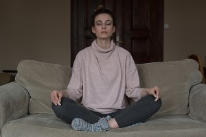 Full length of woman meditating while sitting on sofa