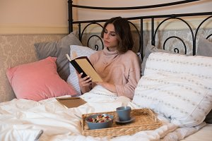 Young woman reading book while sitting on bed