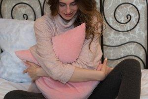 Smiling woman hugging pillow