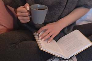 Low section of woman having coffee while sitting on bed