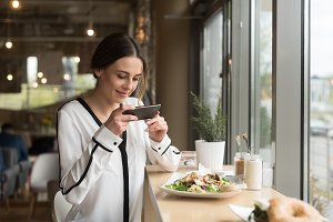 Smiling woman photographing food in plate on table