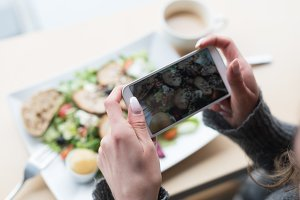 Cropped image of woman photographing salad
