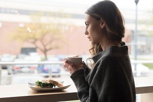 Side view of thoughtful woman having coffee