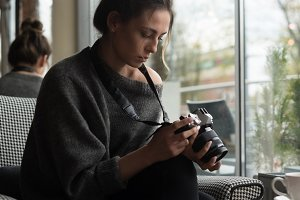 Young woman photographing coffee on table in cafe