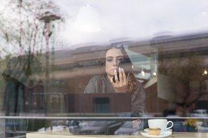 Woman using phone seen through window