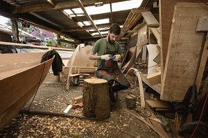 Carpenter shaping wood in workshop